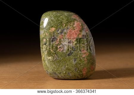 Polished Unakite Gemstone From South Africa Over A Wooden Table