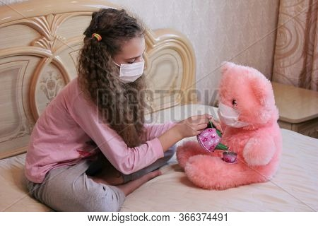 A Girl With A Mask On Her Face Plays At Home On A Bed With A Pink Teddy Bear In A Mask On Her Face.
