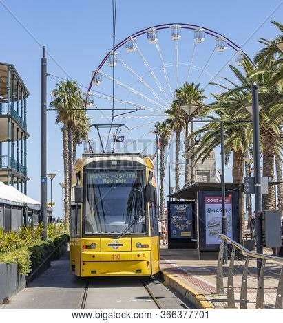 Adelaide, Australia - March 8th, 2020: A Yellow City Tram In Front Of The Ferris Wheel In Adelaide,