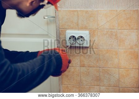 Electrician Repair A Wall Socket At Home Or Office. Closeup Of Man In Workwear Repairing An Electric