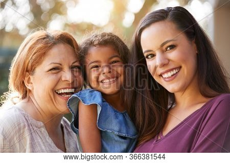 Portrait Of Multi-Generation Female Hispanic Family In Garden Smiling At Camera