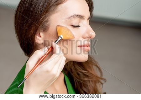 Woman Applying Dry Cosmetic Tonal Foundation On The Face Using Makeup Brush, Beauty With Perfect Nat