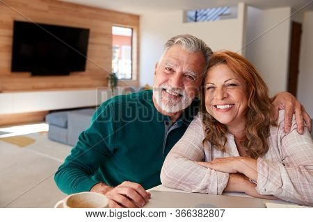 Portrait Of Senior Hispanic Couple At Home Sitting At Table Using Laptop Together