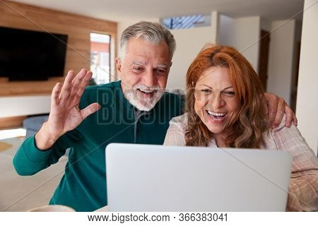 Senior Hispanic Couple At Home With Laptop Having Video Chat With Family