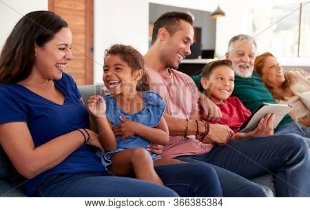 Multi-Generation Hispanic Family Relaxing On Sofa As Grandson Plays With Digital Tablet