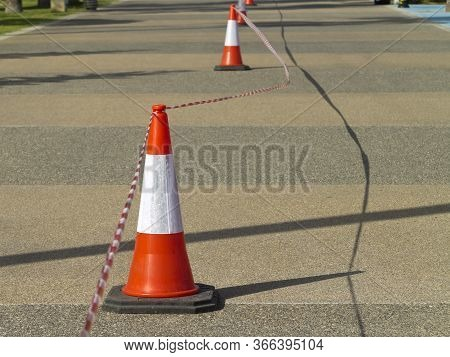 Red And White Striped Traffic Cones With Barricade Tape On The Road In Sunlight
