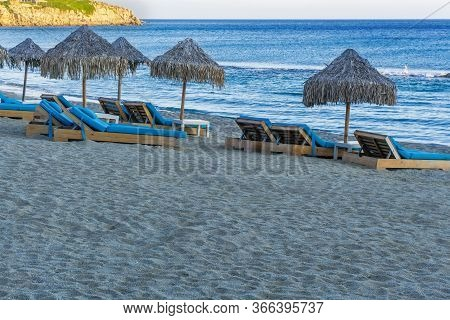 Luxurious Beach Chairs & Umbrellas By An Empty Sandy Beach. Evening View Of Wooden Deck Chairs With