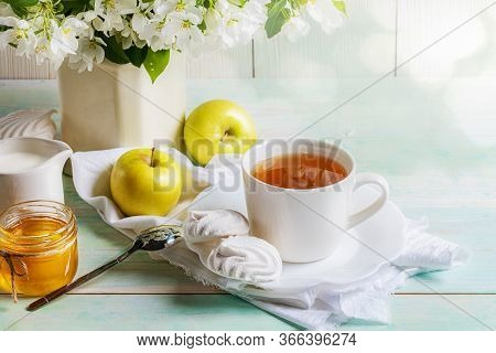 Cup Of Tea With Marshmallows, Honey And Yellow Apples And Apple Tree Blossom Branches In Vase On Woo