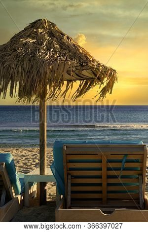 Golden Hour Luxurious Beach Chair & Umbrella By An Empty Sandy Beach. Sea View Of Wooden Deck Chair