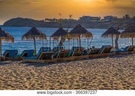 Golden Hour Luxurious Beach Chairs & Umbrellas By Empty Sandy Beach. Wooden Deck Chairs Sea View Wit