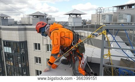 Professional Industrial Climber In An Orange Suit Checks And Sets Rope Insurance On The Roof Of A Bu