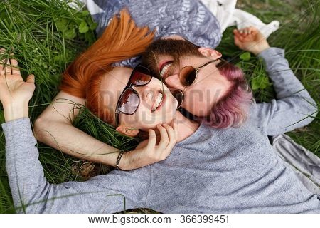 Smiling Hipster Couple, Seated Down On A Green Grass, In Park, Seated Down With Turned Heads, In Sun