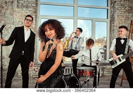 A Multiracial Music Group Performs In A Recording Studio. A Group Of International Musicians Rehears