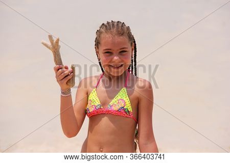 A Happy Girl With African Pigtails Holds A Coral In Her Hand. A Girl In A Bright Swimsuit Is Isolate