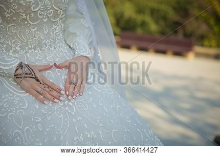 Bride Holds Her Hands On The Belt Of Dress And Ring . Bride Holding On To Belly Hands In Heart-shape