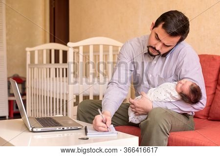 Multitasking Father Working From Home: Man Sitting In Front Of Laptop, Talking On Phone, Rocking Inf