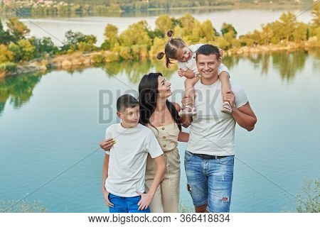 Family Travel With Children Son And Daughter On Vacation Near Lake In Summer. Tourist Enjoying On Va
