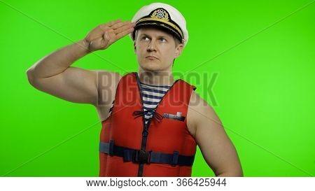 Young Muscular Sailor Man Works As Lifeguard At Beach Salutes With Hand, Looking Up. Seaman Guy Life