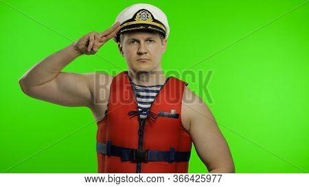 Young Muscular Sailor Man Works As Lifeguard At Beach Salutes With Hand To Camera. Seaman Guy Life S