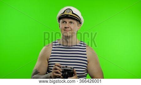 Young Muscular Sailor Man Photographer Takes A Photo On A Retro Camera. Seaman Guy Smiling In Sailor