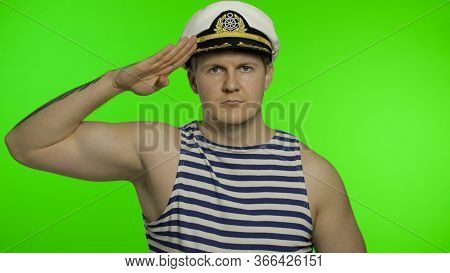 Young Muscular Sailor Man Salutes With Hand To Camera. Seaman Guy Smiling In Sailors Vest. Striped N