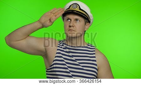 Young Muscular Sailor Man Looking Up Salutes With Hand. Seaman Guy Smiling In Sailors Vests. Striped
