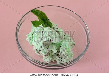 Mint Chocolate Chip Ice Cream In Glass Dessert Bowl With Fresh Mint Leaf Garnish