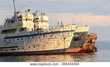 Old Rusty Ships Anchored With Many Birds On Them During Sunset, Port Baikal, Lake Baikal, Russia.