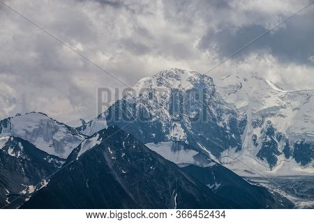Awesome Landscape With Huge Glacial Mountains In Bad Cloudy Weather. Low Stormy Clouds Touch Top Of
