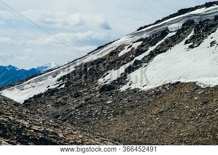 Beautiful Small Glacier With Ice Cornice On Stony Hill Under Cloudy Sky. Snow On Mountain. Firn On R