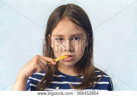 Toddler Smiling While Brushing Her Teeth. Blue Background. A Little Girl Of Caucasian Appearance Bru