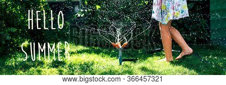 Hello Summer. Child Playing With Garden Sprinkler. Happy Girl In Dress Running And Jumping. Kids Gar