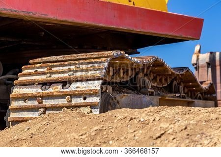 Yellow Excavator During Earthmoving At Open Pit On Blue Sky Background. Construction Machinery And E