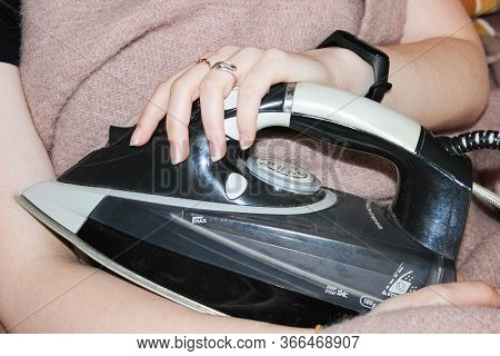 A Woman Is Sitting With Her Arm Around An Old Electric Iron That Is Covered In Dust. The Concept Of