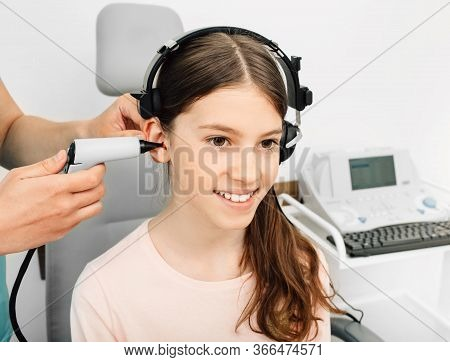 Audiologist Is Doing A Hearing Exam On A Girl. Impedance Audiometry. Methods For Testing The Middle