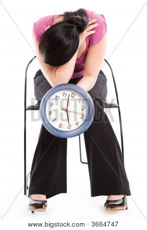 Tired Businesswoman Holding A Clock