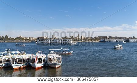 Luxor, Egypt - January 2020: Nile Embankment With Boats And Luxor Temple In Luxor, Beautiful Landsca