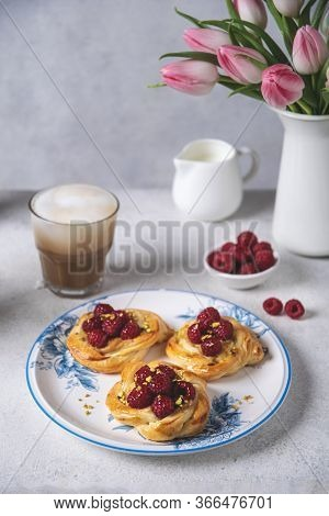 French Pastry, Fresh Baked Buns With Raspberries And Cappuccino Coffee On White Table