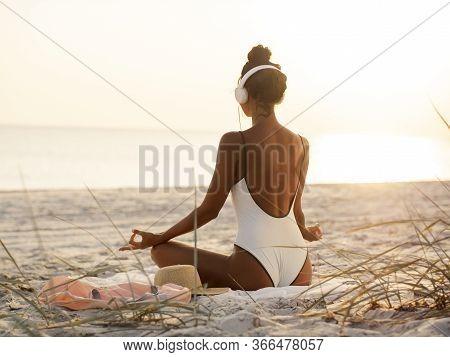 Young Beautiful Woman In Bikini Meditating And Listening To Calm Music In Yoga Lotus Pose On Deserte