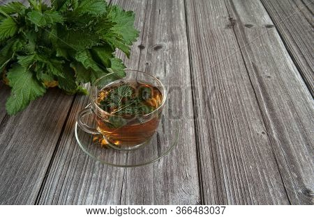 Herbal Tea From Nettle Dioecious In A Glass Cup Close-up On A Wooden Background. Alternative Medicin