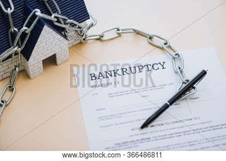 High Angle View Of House Model With Chain Near Pen And Document With Bankruptcy And Chapter 13 Lette