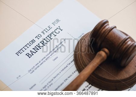 High Angle View Of Gavel On Document With Petition To File For Bankruptcy Lettering Isolated On Beig