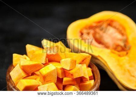 Butternut Squash Pieces In Wooden Bowl, Half Of Pumpkin On Black Background, Closeup, Selective Focu