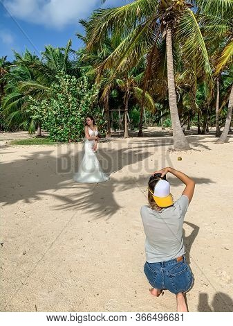 A Professional Photographer Is Taking Photo Of A Beautiful Bride In A White Dress On The Exotic Beac