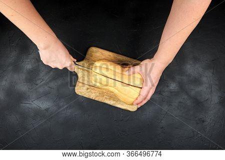 Butternut Squash On Cutting Board On Black Background. Woman Cuts A Whole Sweet Pumpkin (winter Squa