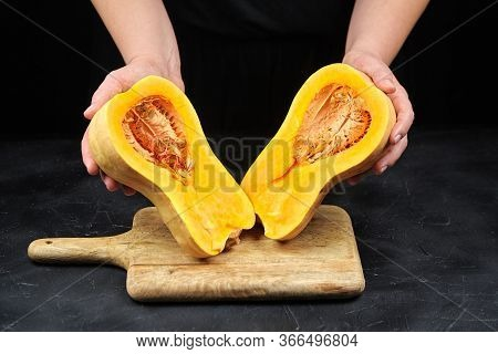 Butternut Squash Halves With Seeds In Female Hands On Black Background, Closeup. Pumpkin Pieces On W
