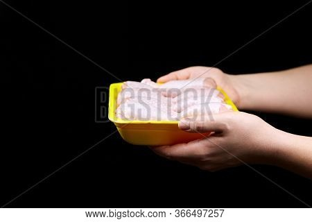 Chicken Shin In Yellow Tray On Black Background With Copy Space. Woman Holds Box With Fresh Chicken