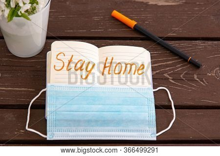 Coronavirus Stay Home Warning Written In Bright Orange Felt-tip Pen In Notepad With Medical Mask. Br