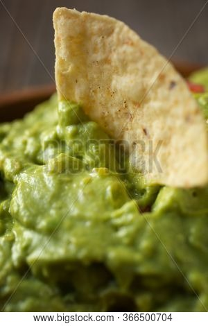 Close up of a nachos chips in a mexican traditional guacamole bowl