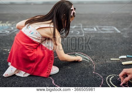 Side View Image Of Little Girl Drawing With Colorful Chalks On Playground. Child Playing The Summer'
